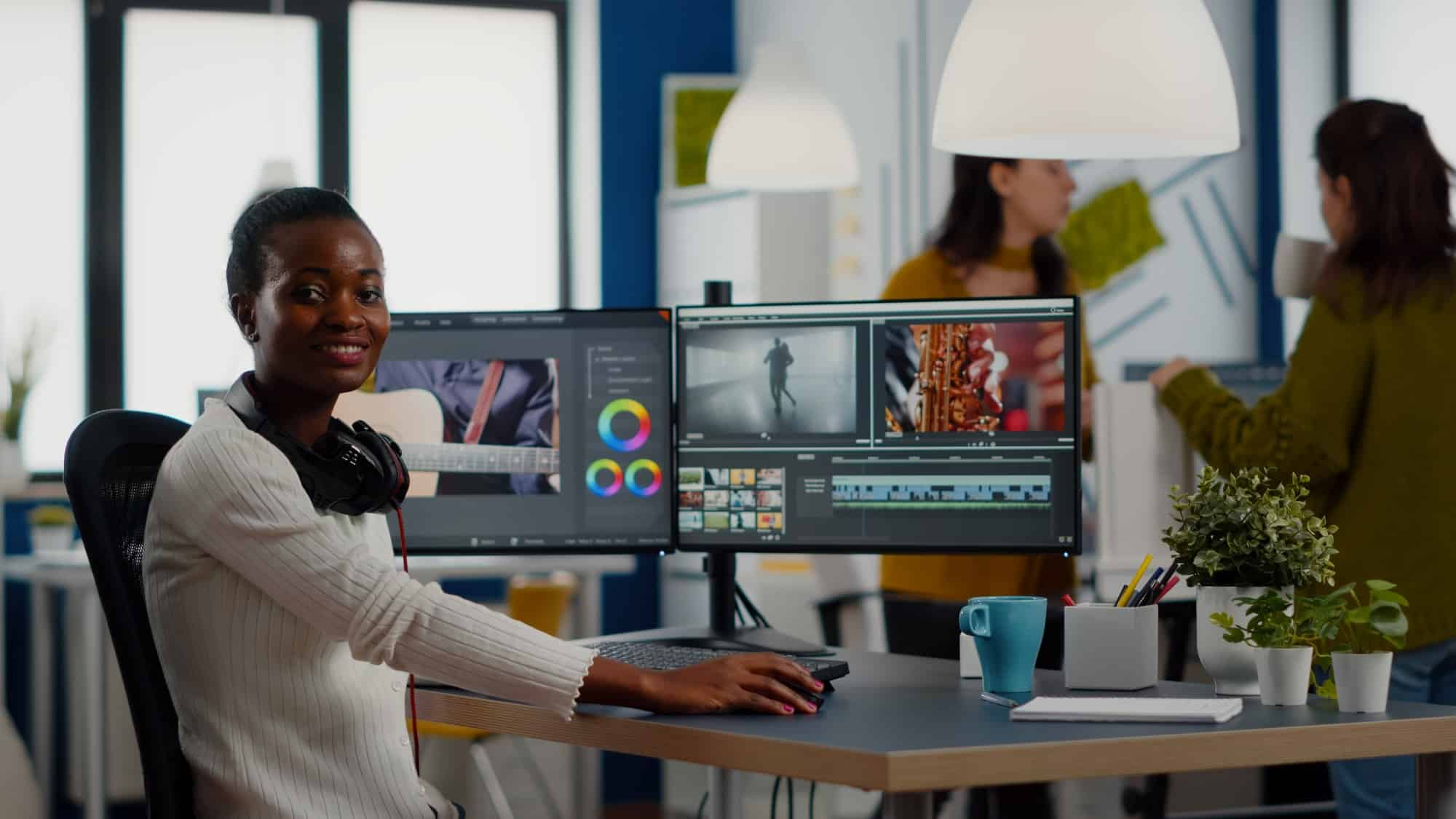 African video editor looking at camera smiling editing video project
